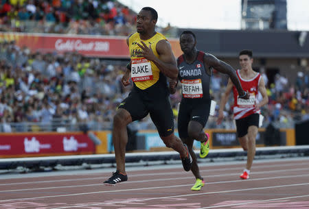 Athletics - Gold Coast 2018 Commonwealth Games - Men's 100m - Heats - Carrara Stadium - Gold Coast, Australia - April 8, 2018. Yohan Blake of Jamaica runs ahead of Sam Effah of Canada. REUTERS/Paul Childs