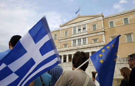 A pro-Euro protestor holds a Greek national flag and a European Union flag during a rally in front of the parliament building, in Athens, Greece, June 30, 2015. REUTERS/Yannis Behrakis