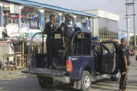 Police officers patrol near the Lekki toll gate in Lagos, Nigeria, Wednesday Oct. 21, 2020. After 13 days of protests against alleged police brutality, authorities have imposed a 24-hour curfew in Lagos, Nigeria's largest city, as moves are made to stop growing violence. ( AP Photo/Sunday Alamba)