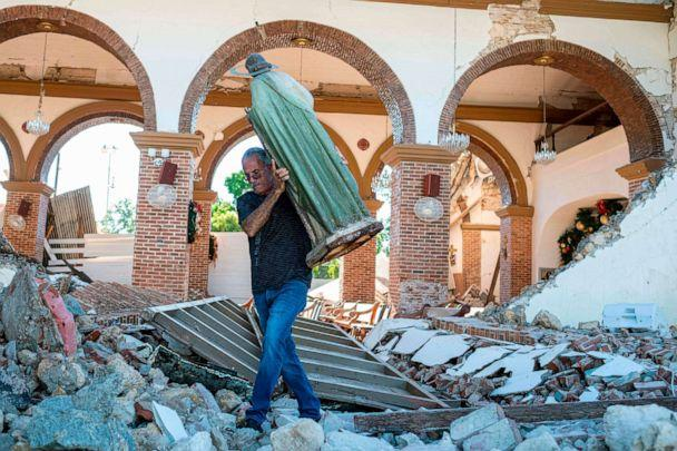 PHOTO: A man carries a St. Jude statue from the Inmaculada Concepcion church ruins that was built in 1841 and collapsed after an earthquake hit the island in Guayanilla, Puerto Rico on Jan. 7, 2020. (AFP via Getty Images, FILE)