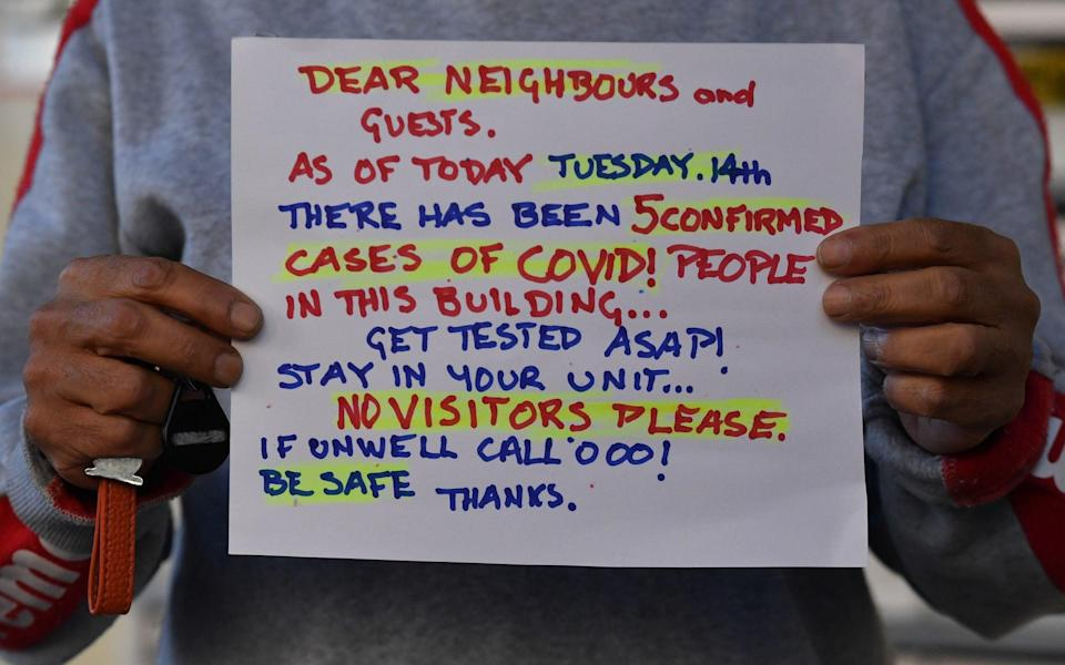 A resident holds up a sign posted in the foyer of a housing block in Darlinghurst, Sydney, New South Wales, Australia, 17 September - DEAN LEWINS/EPA-EFE/Shutterstock