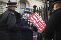 Police speak to anti-Brexit protestor Steve Bray, at the gates of Downing Street, London, Thursday, Dec. 24, 2020. Negotiators from the European Union and Britain worked through the night and into Christmas Eve to put the finishing touches on a trade deal that should avert a chaotic economic break between the two sides next week. Trade will change regardless come Jan. 1, when the U.K. leaves the bloc's single market and customs union. (Victoria Jones/PA via AP)