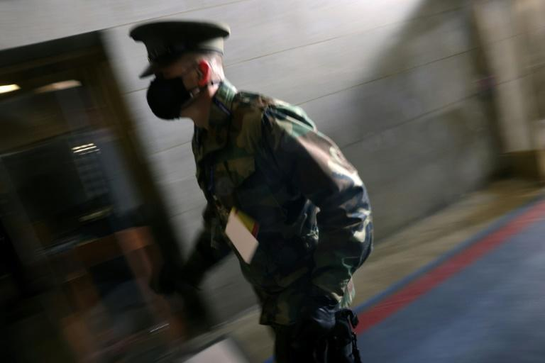 A member of the military rushes during a brief evacuation at the US Capitol
