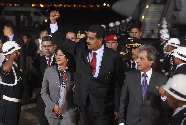 In this photo released by Peru's Presidency Venezuela's President-elect Nicolas Maduro, center, raises his fist next his companion Cilia Flores, left, as they arrive to Lima, Peru, Thursday, April 18, 2013. Maduro, who is to be sworn-in as president in Caracas on Friday, arrived to Lima for an evening meeting of presidents of the Union of South American Nations, UNASUR, to discuss Venezuela's post-election tensions. (AP Photo/Peru's Presidency, Oscar Farje)