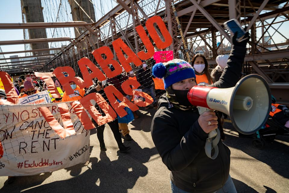 Protestors march across the Brooklyn Bridge to demand funding for excluded workers in the New York State budget on 5 March 2021 (Getty Images)