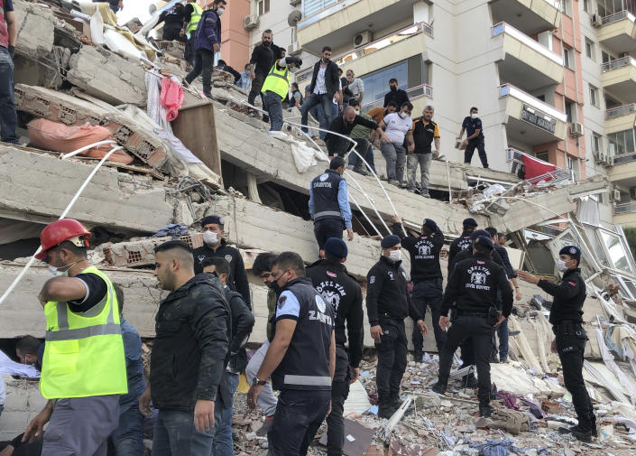 Rescue workers and local people try to save residents trapped in the debris of a collapsed building, in Izmir, Turkey, Friday, Oct. 30, 2020, after a strong earthquake in the Aegean Sea has shaken Turkey and Greece. Turkey's Disaster and Emergency Management Presidency said Friday's earthquake was centered in the Aegean at a depth of 16,5 kilometers (10.3 miles) and registered at a 6.6 magnitude.(AP Photo/Ismail Gokmen)
