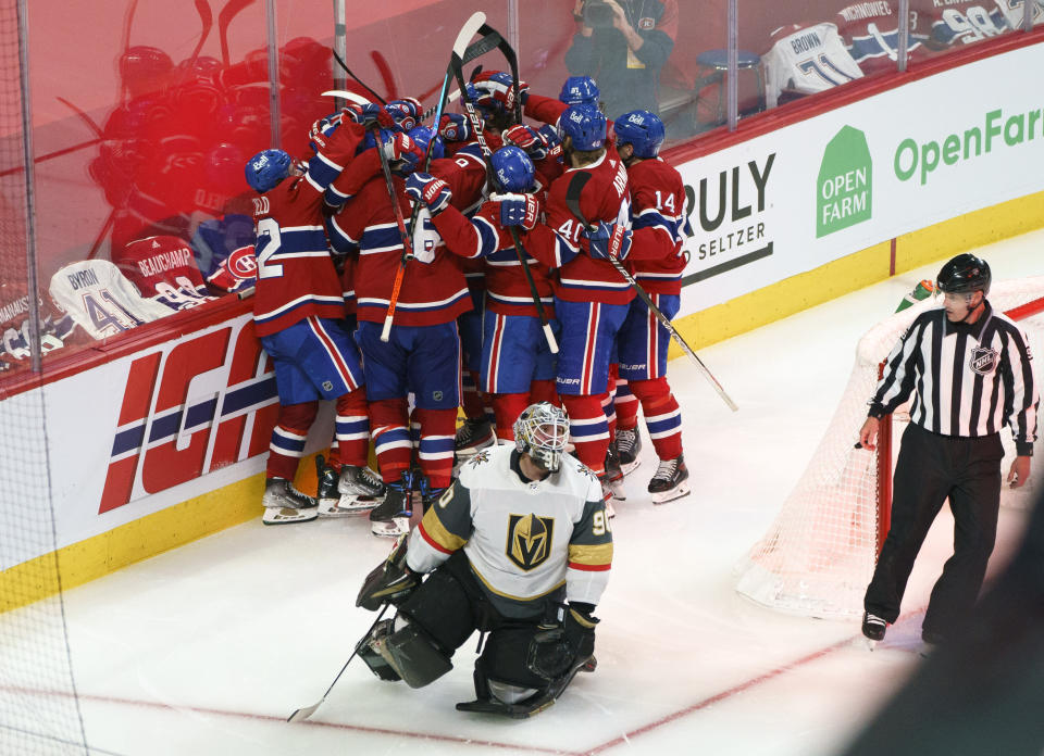 Vegas Golden Knights' Robin Lehner (90) kneels on the ice as Montreal Canadiens' Artturi Lehkonen (62) gets mobbed by teammates in celebration of his game-winning goal following overtime in Game 6 of an NHL hockey Stanley Cup semifinal playoff series Thursday, June 24, 2021 in Montreal. (Paul Chiasson/The Canadian Press via AP)