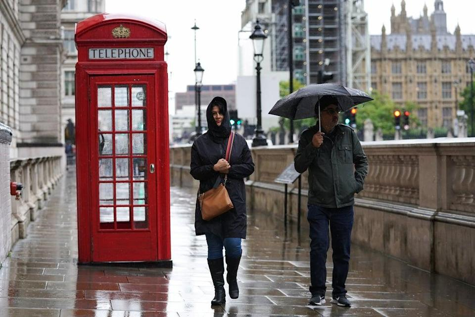 People walk in the rain in Westminster in London as heavy rain and strong winds brought travel disruption and flood warnings to much of the country (Kirsty O'Connor/PA) (PA Wire)