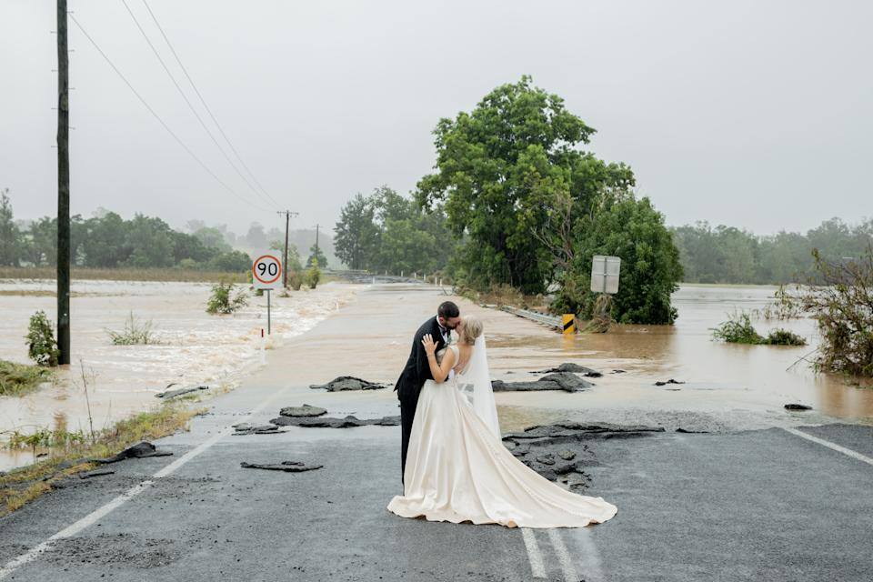Bride and groom kiss in front of flood waters