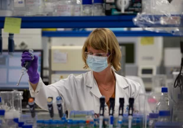 A lab technician conducts research on the novel coronavirus at Johnson & Johnson subsidiary Janssen Pharmaceutical in Beerse, Belgium.  (Virginia Mayo/Associated Press - image credit)