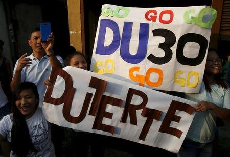 """Supporters of presidential candidate Rodrigo """"Digong"""" Duterte hold placards during election campaigning for May 2016 national elections in Malabon, Metro Manila"""