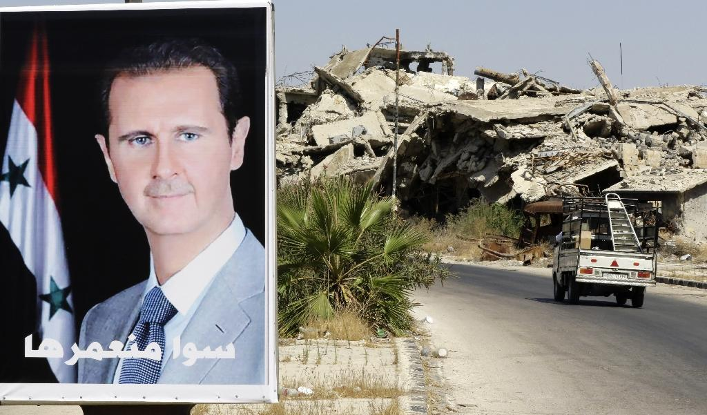 A vehicle drives past a poster of Syrian President Bashar al-Assad and destroyed buildings in the government held Jouret al-Shiah neighbourhood of the central Syrian city of Homs on September 19, 2016 (AFP Photo/Louai Beshara)