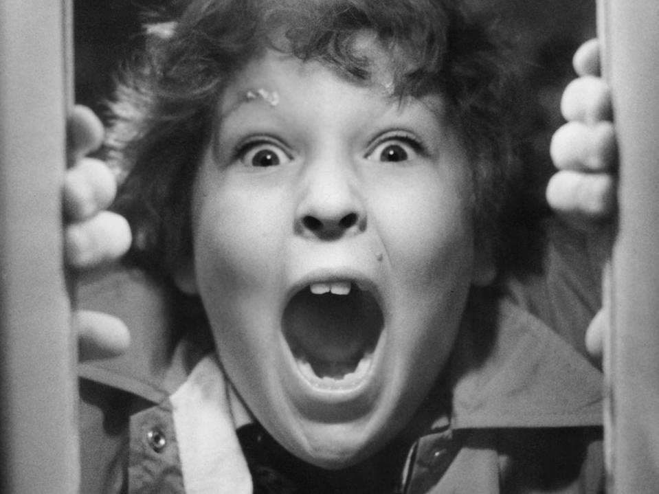 """Jeff Cohen shouting through a hole in the door in a scene from """"The Goonies."""""""