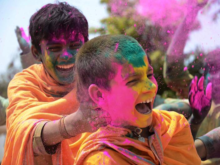 Students celebrate the festival of Holi in Jabalpur, in the Indian state of Madhya Pradesh (21 March 2019): UMA SHANKAR MISHRA/AFP via Getty Images