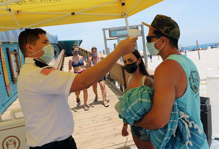 People at Cocoa Beach, Florida, get their temperature checked on July 4, 2020.