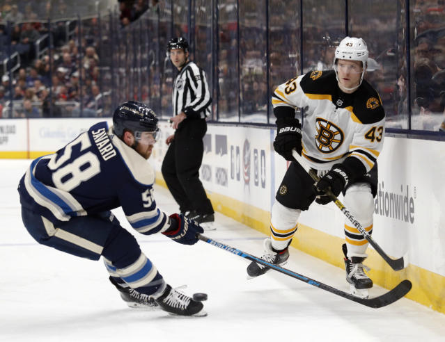 Boston Bruins forward Danton Heinen, right, passes in front of Columbus Blue Jackets defenseman David Savard during the first period of an NHL hockey game in Columbus, Ohio, Tuesday, Jan. 14, 2020. (AP Photo/Paul Vernon)