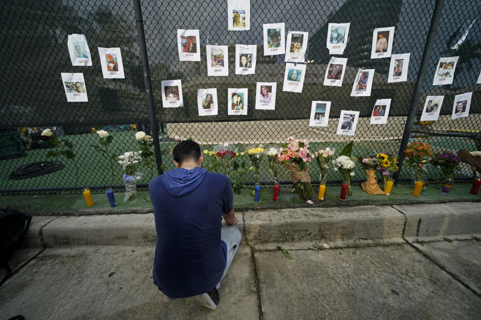 Leo Soto, who created this memorial with grocery stores donating flowers and candles, pauses in front of photos of some of the missing people that he put on a fence, near the site of an oceanfront condo building that partially collapsed in Surfside, Fla., Friday, June 25, 2021. (AP Photo/Gerald Herbert)