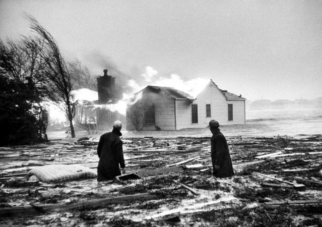 <p>Two people watch a house burn in aftermath of Hurricane Hazel in October, 1954. (Photo from Hank Walker/The LIFE Picture Collection/Getty Images) </p>