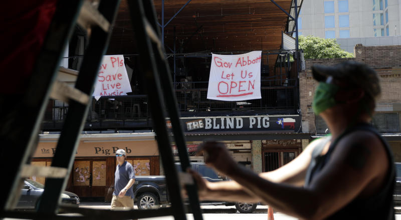 Signs directed at Texas Gov. Greg Abbott hang on a pub behind workers preparing another pub that they hope to reopen soon in Austin, Texas, Monday, May 18, 2020. Texas continues to go through phases as the state reopens after closing many non-essential businesses to help battle the spread of COVID-19. (AP Photo/Eric Gay)