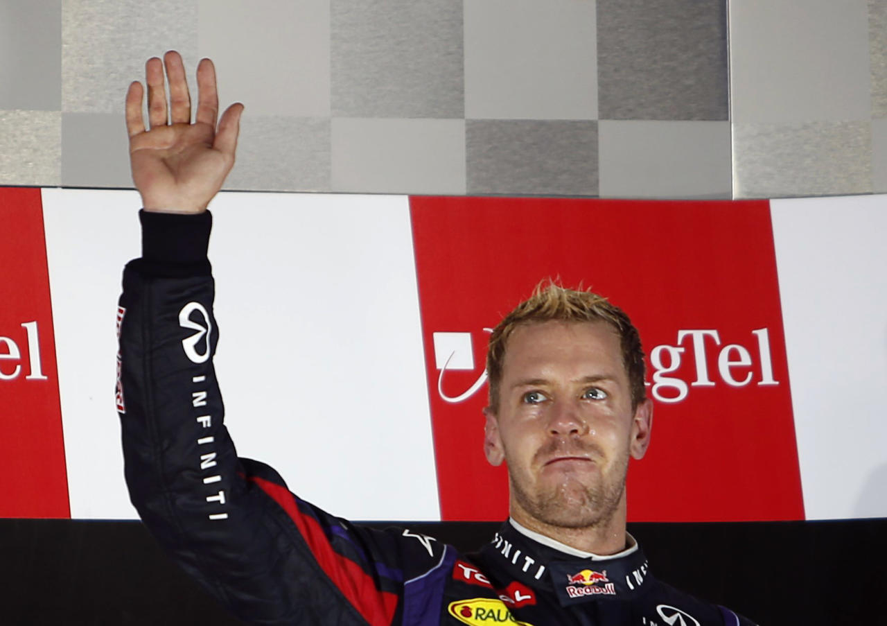 Red Bull Formula One driver Sebastian Vettel of Germany waves on the podium after winning the Singapore F1 Grand Prix at the Marina Bay street circuit in Singapore September 22, 2013. REUTERS/Tim Chong (SINGAPORE - Tags: SPORT MOTORSPORT F1)