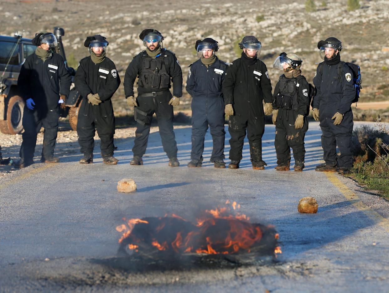 Israeli policemen stand next to a burning tyre on a road near the entrance to the Israeli settler outpost of Amona.
