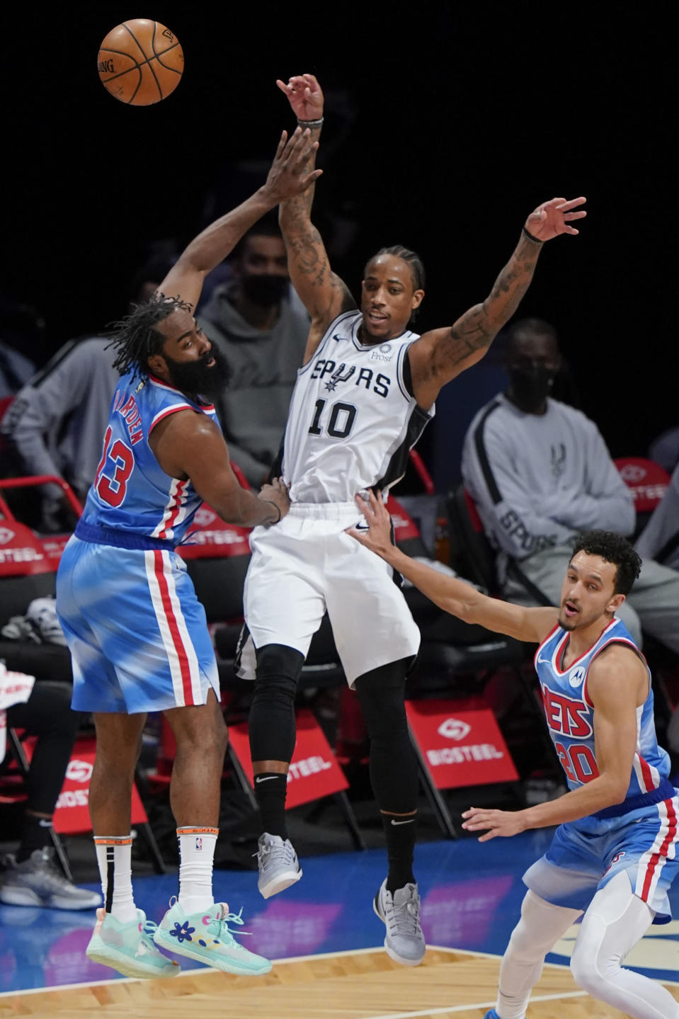 San Antonio Spurs' DeMar DeRozan (10) passes away from Brooklyn Nets' James Harden (13) and Landry Shamet (20) during the second half of an NBA basketball game Wednesday, May 12, 2021, in New York. (AP Photo/Frank Franklin II)