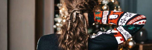 photo of woman with back to camera and hand in hair in front of christmas tree
