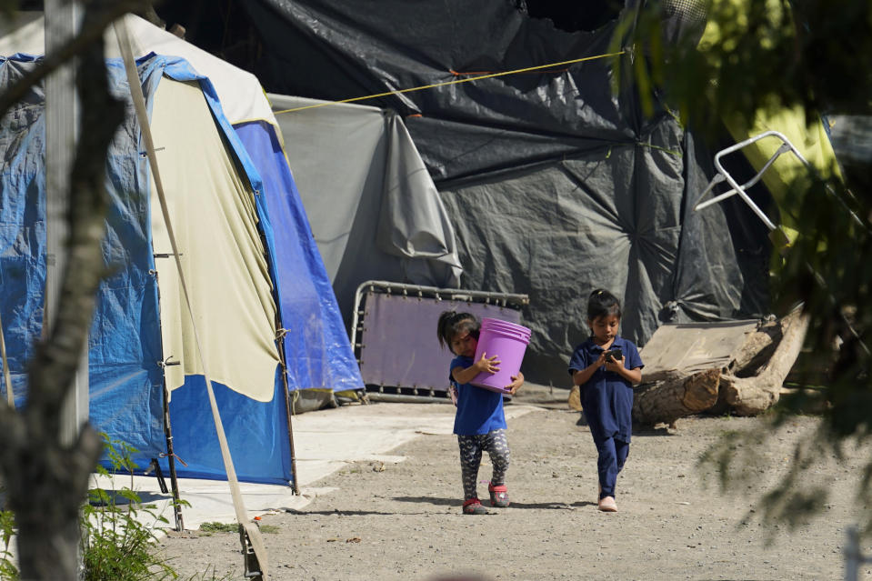 Children walk through a camp of asylum seekers stuck at America's doorstep, in Matamoros, Mexico, Wednesday, Nov. 18, 2020. Led by U.S. military veterans, Global Response Management is staffed by volunteers primarily from the U.S. and paid asylum seekers who were medical professionals in their homelands. The group has treated thousands of migrants over the past year at two clinics in Matamoros, including one inside the camp. (AP Photo/Eric Gay)