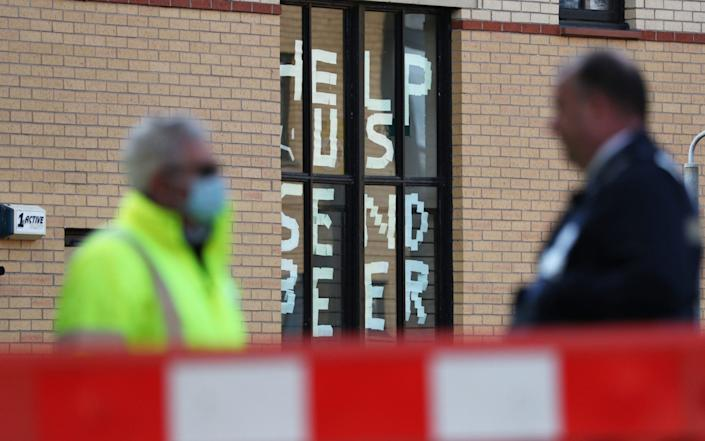 A sign saying 'help us, send beer' at Murano Street Student Village in Glasgow, where Glasgow University students are being tested at a pop up test centre - Andrew Milligan/PA