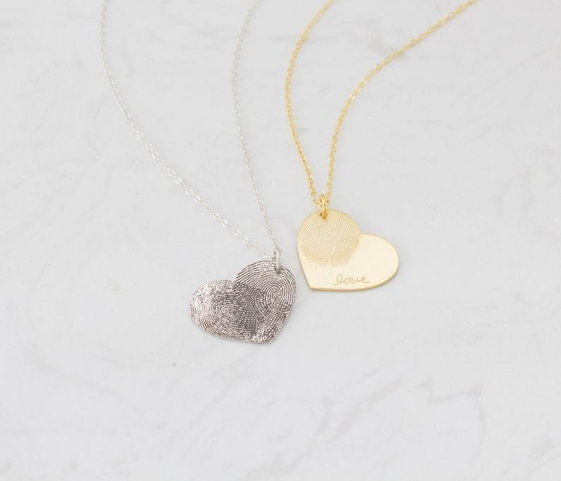 """<p><strong>SilverHandwriting</strong></p><p>etsy.com</p><p><strong>$30.75</strong></p><p><a href=""""https://go.redirectingat.com?id=74968X1596630&url=https%3A%2F%2Fwww.etsy.com%2Flisting%2F472670772%2Fcustom-fingerprint-necklace-heart-charm&sref=https%3A%2F%2Fwww.oprahdaily.com%2Flife%2Fg31400004%2Funique-mothers-day-gifts%2F"""" rel=""""nofollow noopener"""" target=""""_blank"""" data-ylk=""""slk:SHOP NOW"""" class=""""link rapid-noclick-resp"""">SHOP NOW</a></p><p>With your fingerprints immortalized on a pretty personalized necklace, mom will—quite literally—always carry a piece of you with her. </p>"""