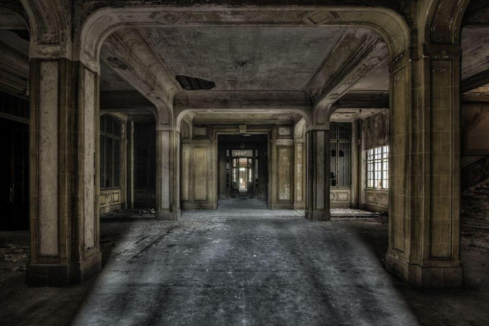 <p>Tall pillars cast ominous shadows in this former reception space.</p>