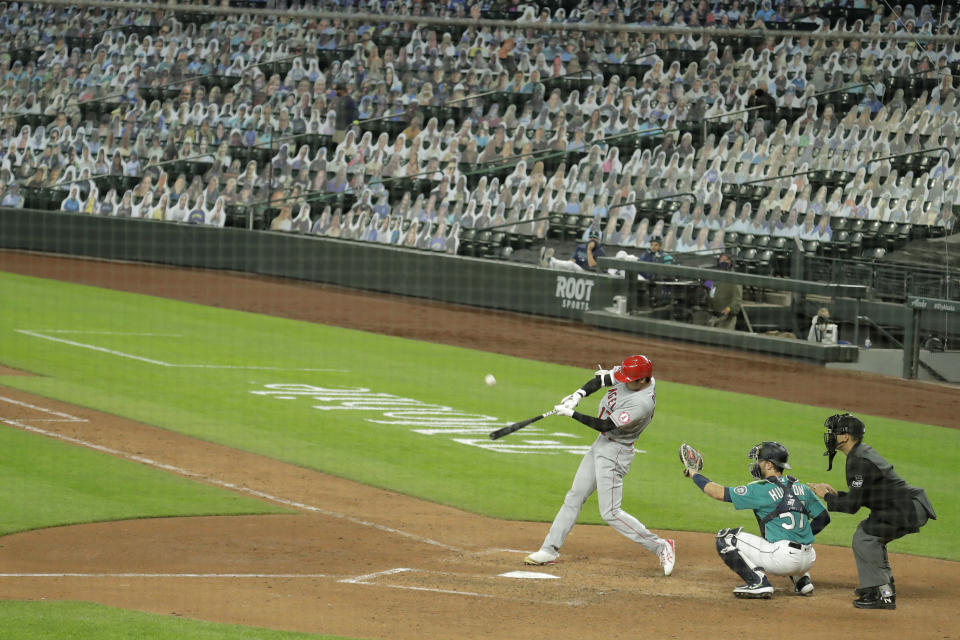 With photos of fans filling the seats at Safeco Field, Los Angeles Angels' Shohei Ohtani flies out to center field to end the top the seventh inning of a baseball game against the Seattle Mariners, Thursday, Aug. 6, 2020, in Seattle. (AP Photo/Ted S. Warren)