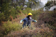 A Turkish volunteer tries to find a way through the bush as they fight wildfires in Turgut village, near tourist resort of Marmaris, Mugla, Turkey, Wednesday, Aug. 4, 2021. As Turkish fire crews pressed ahead Tuesday with their weeklong battle against blazes tearing through forests and villages on the country's southern coast, President Recep Tayyip Erdogan's government faced increased criticism over its apparent poor response and inadequate preparedness for large-scale wildfires.(AP Photo/Emre Tazegul)