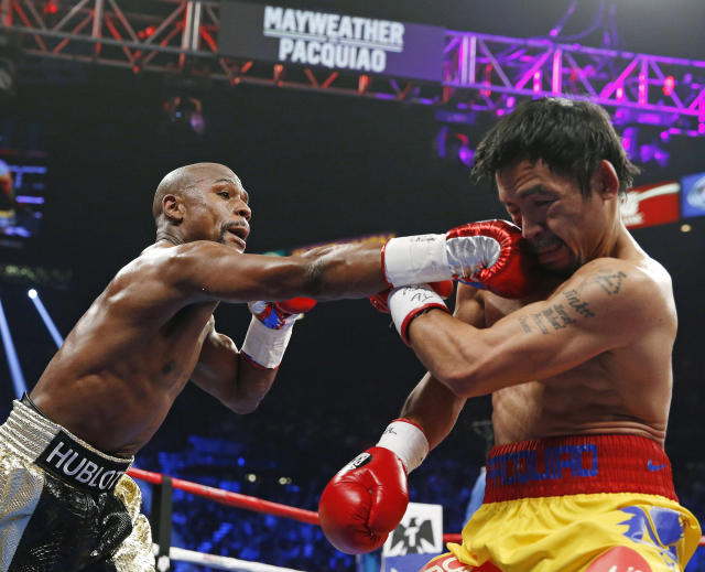 FILE - In this May 2, 2015, file photo, Floyd Mayweather Jr., left, connects with a right to the head of Manny Pacquiao, from the Philippines, during their welterweight title fight in Las Vegas. Mayweather Jr. says he's coming out of retirement again to fight Pacquiao for a second time in December. Mayweather posted a video on Instagram early Saturday, ept. 15, 2018, that showed Pacquiao and him together, reportedly in Japan, jawing at each other over a possible second fight. Representatives for the two fighters could not immediately be reached for comment. (AP Photo/John Locher, File)