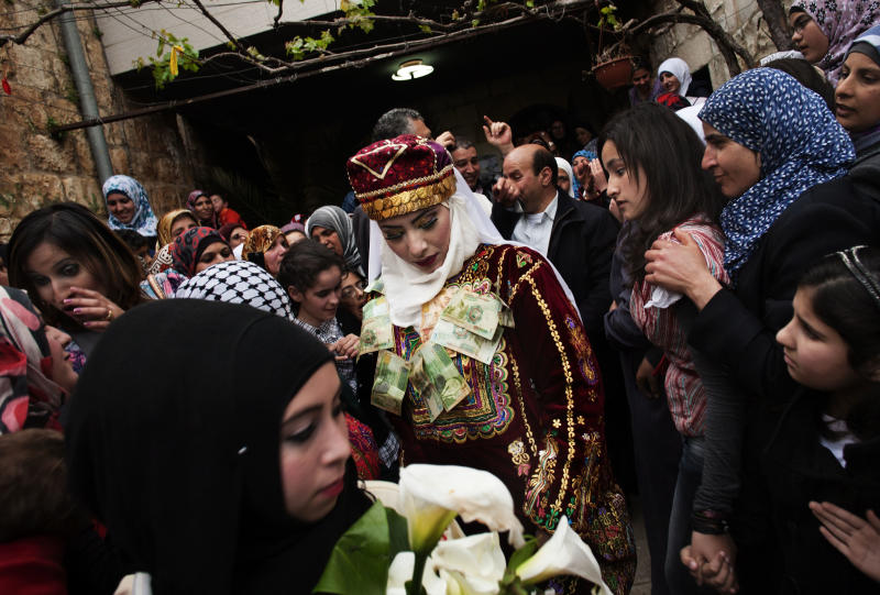 In this photograph made on Thursday, April 12, 2012, bride Maha Surougi walks towards Thaer Qasem, the groom, during their wedding in the West Bank village of Deir Istiya, near Nablus. The bride and the groom, Syrian citizens with Palestinian roots were invited by the Palestinian government to celebrate their marriage in the West Bank. (AP Photo/Bernat Armangue)