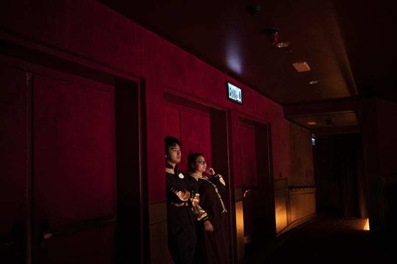 In this Oct. 11, 2019 photo, two workers stand inside a theater during a play in Hong Kong Disneyland in Hong Kong. The body-blow of months of political protests on Hong Kong's tourism is verging on catastrophic for one of the world's great destinations. Geared up to receive 65 million travelers a year, the city's hotels, retailers, restaurants and other travel-oriented industries are suffering. But some intrepid visitors came specifically to see the protests and are reveling in deep discounts and unusually short lines at tourist hotspots.(AP Photo/Felipe Dana)