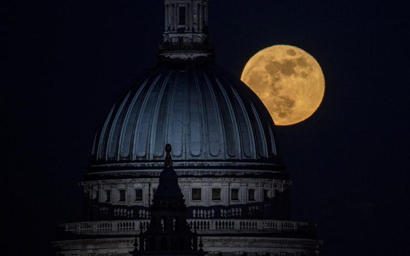 The moon rises behind St Paul's, London - Getty Images