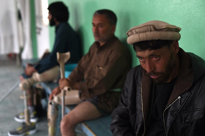 Afghan men wearing prosthetics after losing their legs in landmine explosions sit at a hospital of the International Committee of the Red Cross in March 2019. Talks are underway to end Afghanistan's long-running war (AFP Photo/WAKIL KOHSAR)