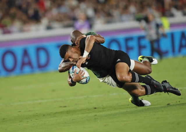 New Zealand's Richie Mo'unga is tackled by South Africa's Makazole Mapimpi during the Rugby World Cup Pool B game between New Zealand and South Africa in Yokohama, Japan, Saturday, Sept. 21, 2019. (AP Photo/Shuji Kajiyama)