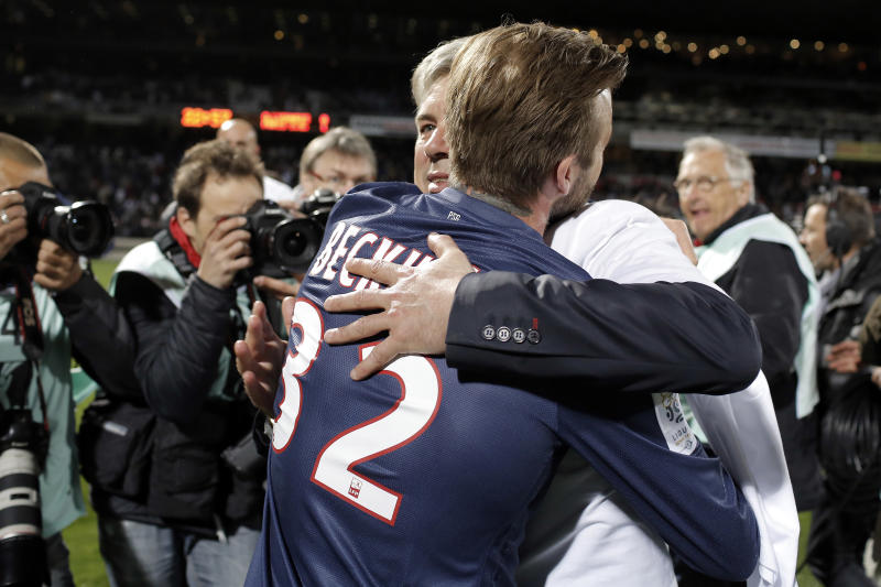Paris Saint Germain's coach Carlo Ancelotti celebrates the title with player David Beckham, left, after winning their French League One soccer match against Lyon, in Lyon, central France, Sunday, May 12, 2013. (AP Photo/Laurent Cipriani)