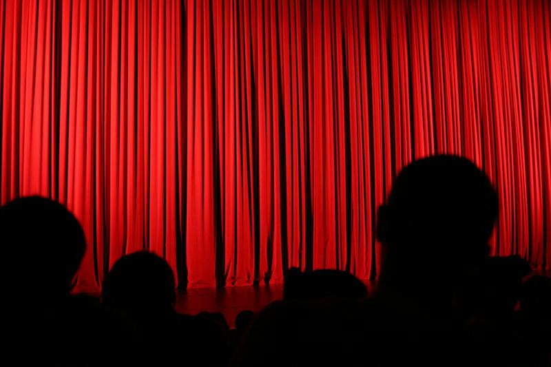 An audience facing the stage during an intermission with the curtains drawn.