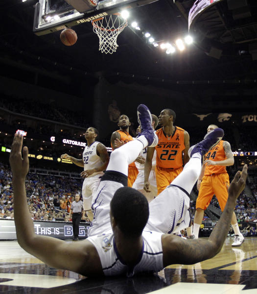 Kansas State forward Jordan Henriquez, foreground, is knocked to the floor after blocking a shot by Oklahoma State guard Markel Brown (22) during the first half an NCAA college basketball game in the Big 12 men's tournament on Friday, March 15, 2013, in Kansas City, Mo. (AP Photo/Charlie Riedel)