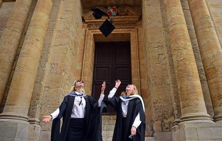 Graduates throw their mortar boards in the air after a graduation ceremony at Oxford University, in Oxford
