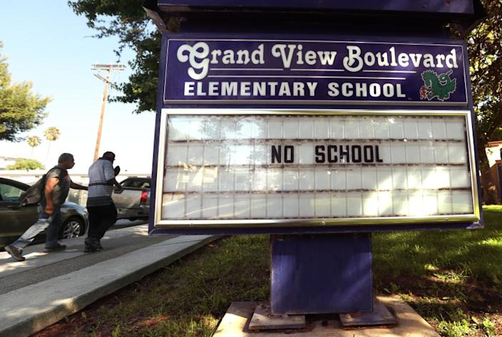 "People walk past the Grand View Boulevard Elementary School marquee in Mar Vista on July 13. <span class=""copyright"">(Genaro Molina / Los Angeles Times)</span>"