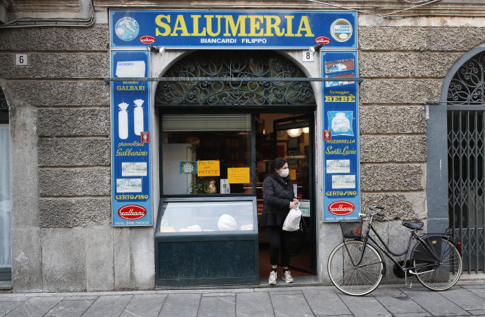 In this photo taken on Thursday, March 12, 2020, a woman gets out of a deli meat and cold cuts shop in Codogno, Italy. The northern Italian town that recorded Italy's first coronavirus infection has offered a virtuous example to fellow Italians, now facing an unprecedented nationwide lockdown, that by staying home, trends can reverse. Infections of the new virus have not stopped in Codogno, which still has registered the most of any of the 10 Lombardy towns Italy's original red zone, but they have slowed. For most people, the new coronavirus causes only mild or moderate symptoms. For some it can cause more severe illness. (AP Photo/Antonio Calanni)
