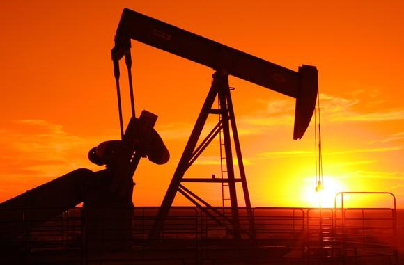 An oil pump jack in front of an orange sunset.