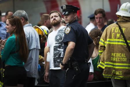 An injured tourist is assisted by emergency personnel following a collision between two tour buses in the Times Square region of New York August 5, 2014. REUTERS/Mike Segar