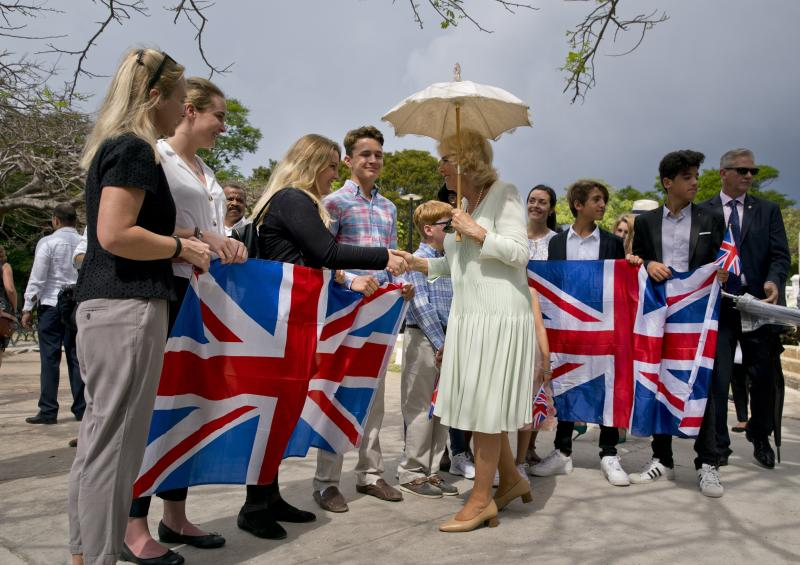 Camilla, Duchess of Cornwall, greets a group of people holding United Kingdom's national flags during a cultural event in Havana, Cuba, Tuesday, March 26, 2019. Prince Charles and Camilla arrived in Cuba Sunday with an agenda including visits to historic sites, a solar park, organic farm, bio-medical research center, a meeting with entrepreneurs, a cultural gala and a dinner with Cuba's president. (AP Photo/Ramon Espinosa)
