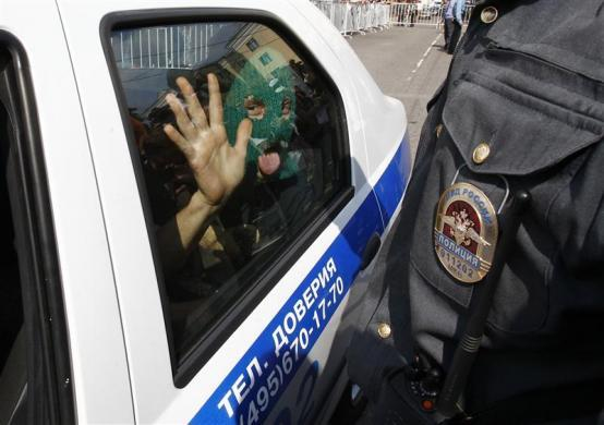 "A supporter of members of the female punk band ""Pussy Riot"" reacts inside a police car after being detained for taking part in an unsanctioned rally outside a court building in Moscow, August 17, 2012."