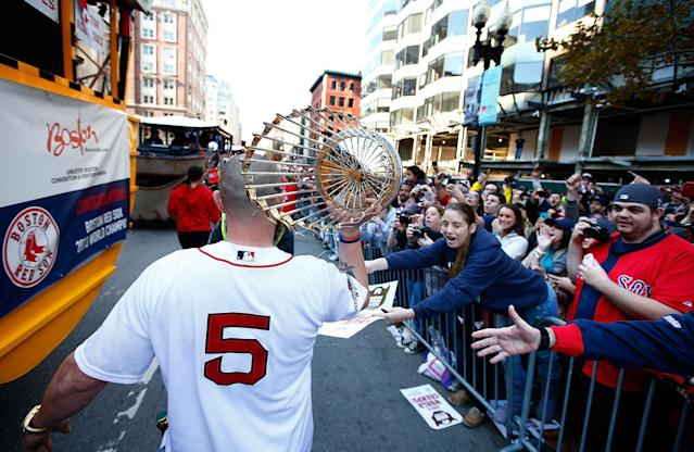 BOSTON, MA - NOVEMBER 02: Jonny Gomes #5 carries the World Series trophy near the finish line of the Boston Marathon on Boylston Street during the World Series victory parade on November 2, 2013 in Boston, Massachusetts. (Photo by Jared Wickerham/Getty Images)